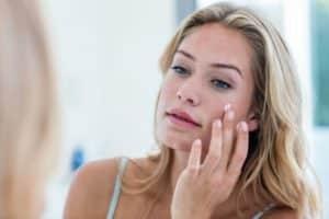 Titelbild - Gesichtscreme ab 30 Jahren - Frau cremt sich die Wangen ein