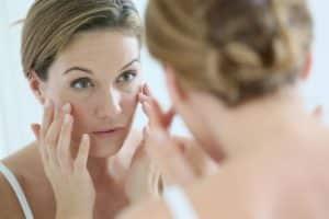 Frau mittleren Alters cremt sich die Wangen mit Gesichtscreme ein