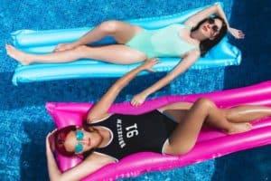 Zwei Frauen liegen im Pool auf einer Luftmatratze. - Pflege fuer reife Haut ab 50 - Sonnenbaden und Sonnenbänke