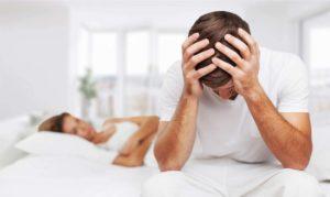 Man sitzt auf dem Bett und kann nicht schlafen - Zu wenig Schlaf und viel Stress